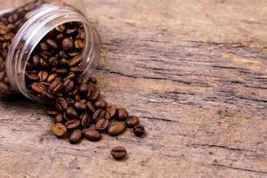 grãos de café aromáticos caíram de uma jarra de vidro foto