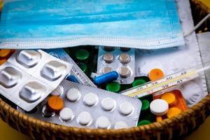 cesta de vime cheia de suprimentos médicos e medicamentos foto