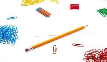 lápis, borracha, apontador e clipes de papel em um fundo branco foto
