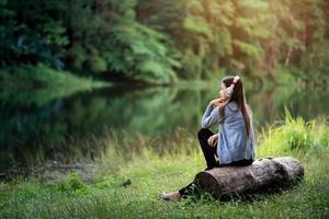 bela jovem com fones de ouvido relaxantes perto do rio foto