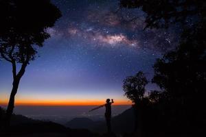 silhueta de um fotógrafo profissional que fotografa a Via Láctea nas montanhas foto