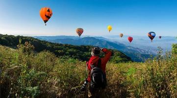 fotógrafo profissional tira fotos de paisagens em uma montanha com balões de ar quente ao fundo