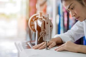mulher está costurando com uma máquina de costura em casa enquanto está sentada em seu local de trabalho foto