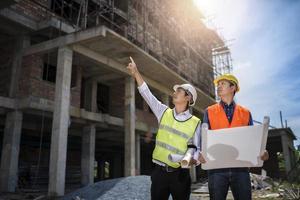 empresário e engenheiro olhando para a planta de um prédio em um canteiro de obras foto