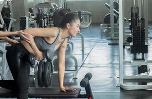 linda mulher asiática se exercitando em uma academia foto