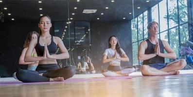 grupo fazendo ioga na academia por meio de alongamento, conceito de exercício saudável foto