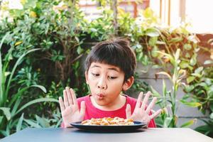 criança asiática fofa mostrou uma boa expressão quando viu uma pizza em um prato foto