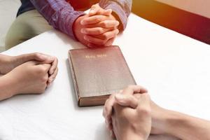 grupo cristão sentado em uma igreja estudando a palavra de Deus com uma Bíblia no meio foto