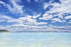 vista panorâmica do mar azul e céu azul no verão com colinas ao fundo foto