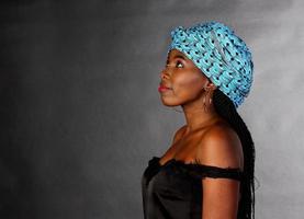 negra jovem com lenço azul olhando para cima, foto de estúdio, mulher africana
