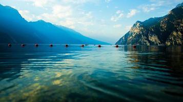 lago garda com bóias vermelhas e montanhas como pano de fundo em riva del garda, trento, itália foto