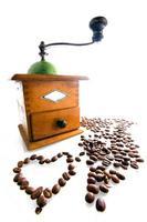 moedor de café com grãos de café isolados no branco foto