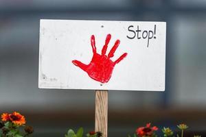 sinal com a mão pintada de vermelho preso em um canteiro de flores na frente do fundo desfocado foto