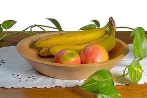 mão virou tigela de madeira com bananas e carrinhos de maçã em uma mesa foto