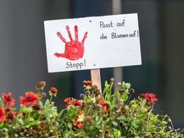 sinal com mão pintada de vermelho preso em um canteiro de flores com a inscrição em alemão. foto