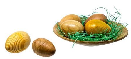 mão virando ovos de madeira em uma pequena tigela de madeira foto