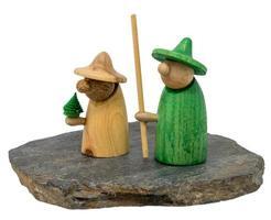 duas figuras de natal de madeira em uma placa de madeira escura foto