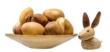 mão virando ovos de madeira em uma pequena tigela de madeira com coelhinhos da Páscoa de brinquedo foto