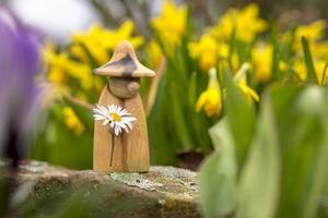 figura de elfo de madeira com uma margarida na mão em um canteiro de flores em frente a flores desfocadas foto