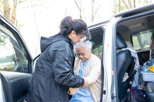 ajuda e suporte mulher idosa asiática ou paciente idosa sentada na cadeira de rodas prepare-se para chegar ao carro foto
