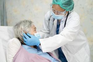 médico usando estetoscópio para verificar paciente mulher idosa ou idosa asiática usando máscara facial no hospital para proteção contra infecção covid 19 coronavírus foto