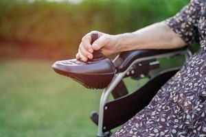 paciente idosa ou idosa asiática em cadeira de rodas elétrica com controle remoto na enfermaria do hospital foto
