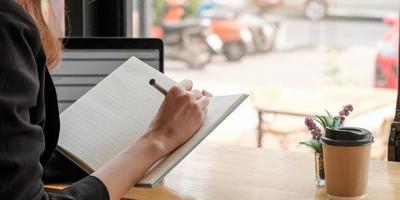 close-up de mulher, estudo online distante no laptop, anote, escreva no caderno, sentado na mesa em casa, escritora inteligente ou estudante escrita à mão no bloco de notas planejando papelaria foto