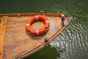 bóia salva-vidas laranja na proa de um pequeno barco de madeira foto