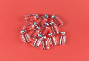 muitos frascos com remédio líquido em fundo vermelho foto