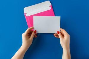 envelope rosa com um cartão em branco nas mãos sobre um fundo azul foto