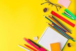 configuração plana de papelaria em fundo amarelo de volta ao conceito de escola foto