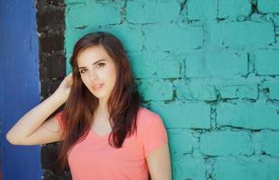 garota sorridente com cabelo castanho perto de uma parede colorida foto
