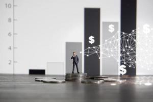 empresário de conceito de negócio em pé sobre uma pilha de moedas de prata foto