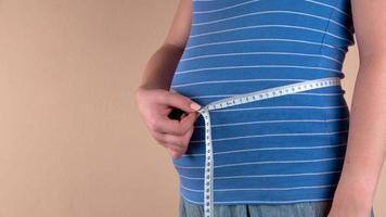 lindo corpo de mulher grávida com fita métrica foto