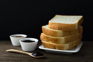fatias de pão torrado em um único prato branco na mesa de madeira com fundo preto e geleia de groselha preta no copo pequeno e na colher de pau foto