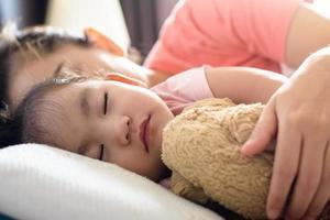 Feche a linda menina asiática e a mãe dela dormindo na cama foto