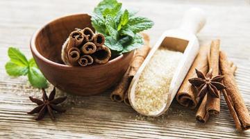 Paus de canela de anis estrelado e açúcar mascavo em uma mesa de madeira foto