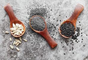 colheres de pau com várias sementes saudáveis foto