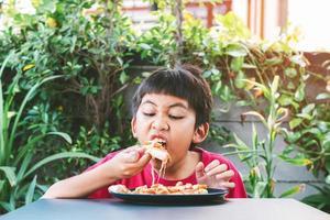 menino asiático fofo sentado feliz comendo pizza foto