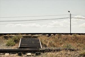 uma escada de ferro através da ferrovia foto