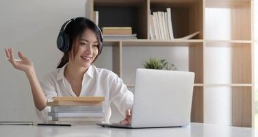 vista lateral, tiro na cabeça, mulher mestiça sorridente usando fone de ouvido, comunicando-se com o cliente por vídeo chamada foto