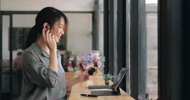 close-up de uma jovem asiática usando fones de ouvido sem fio para fazer cursos de idiomas on-line e pesquisar informações por meio de um laptop em um café foto