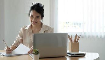 Feliz jovem empresário asiático usando computador olhando para a tela trabalhando na internet sente-se na mesa do escritório, sorrindo, funcionária profissional, digitando e-mail no laptop no local de trabalho foto