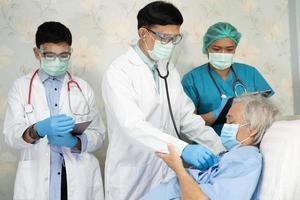equipe médica asiática verifica paciente idosa idosa quanto à doença para motivação novo normal para tratar infecção covid 19 coronavírus na enfermaria do hospital foto