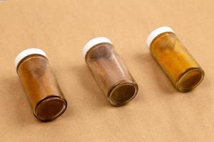 três potes de tempero em um fundo marrom com foco seletivo foto