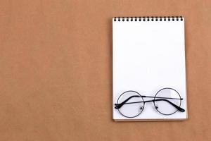 vista de cima plana de óculos e bloco de notas em um fundo bege foto