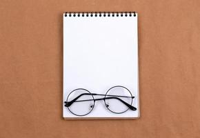 foto de vista superior plana de óculos e bloco de notas em um fundo bege abstrato com estilo mínimo de espaço de cópia