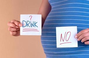 barriga de uma mulher grávida em uma camiseta azul com as palavras bebida e não foto