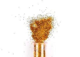 frasco com sombras brilhantes de glitter dourado derramado sobre fundo branco foto