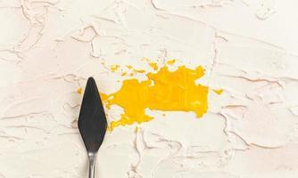 uma faca de paleta de pintura isolada em um fundo pintado de creme pintando de amarelo com espaço de cópia foto